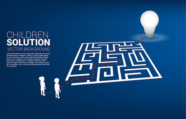Silueta de niño y niña con ruta de acceso para salir del laberinto a la bombilla. concepto de solución educativa y futuro de los niños.