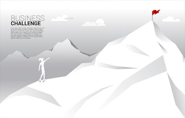 Silueta del punto de la empresaria a la bandera en la cima de la montaña. concepto de ruta hacia el éxito. meta misión visión éxito en carrera.