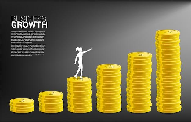 Silueta del punto de la empresaria a una pila más alta de moneda.