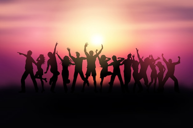 Siluetas de personas bailando en un paisaje al atardecer.