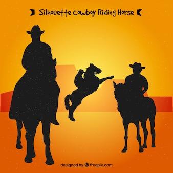 Siluetas de vaqueros montando caballo