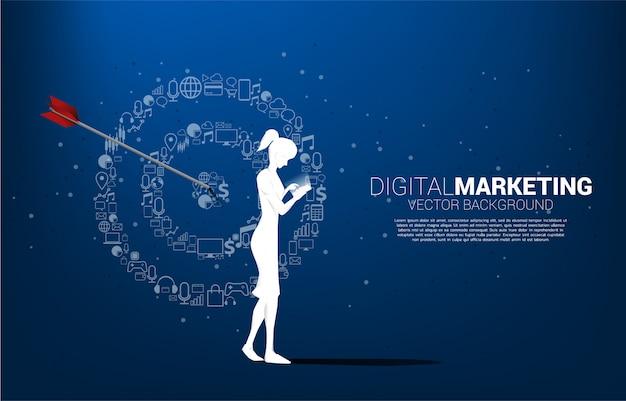 Siluetee a la mujer con el teléfono móvil con el tablero de dardos del punto del icono de la comercialización. concepto de negocio de marketing objetivo y cliente