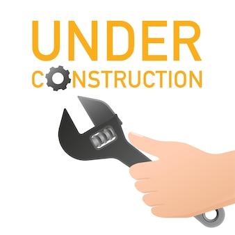El sitio está en construcción con llave y pancarta de mano.