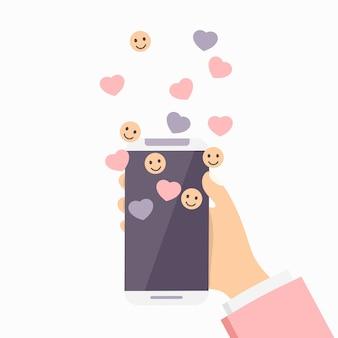 Smartphone en mano con iconos de sonrisa, me gusta y notificación.