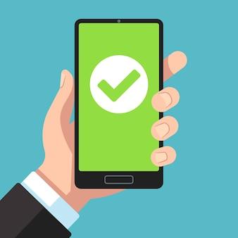Smartphone de mano con marca de verificación verde