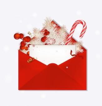 Sobre rojo abierto con tarjeta de felicitación navideña, bastón de caramelo, ramas de abeto, bayas rojas, decoración navideña