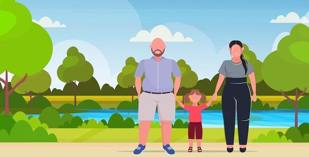 Sobrepeso familia tomados de la mano madre padre e hija juntos de pie sobre el tamaño de los padres con el niño divirtiéndose fondo del paisaje del parque de verano de longitud completa horizontal plana