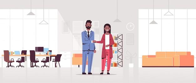 Socios comerciales hombre mujer apretón de manos pareja apretón de manos durante la reunión acuerdo asociación concepto moderno centro de trabajo compartido oficina interior horizontal de longitud completa