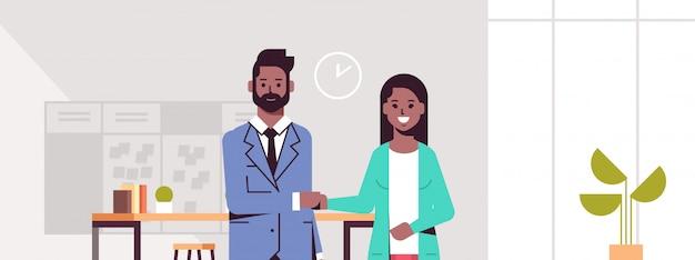 Socios comerciales hombre mujer apretón de manos pareja apretón de manos durante la reunión acuerdo asociación concepto moderno centro de trabajo oficina interior horizontal