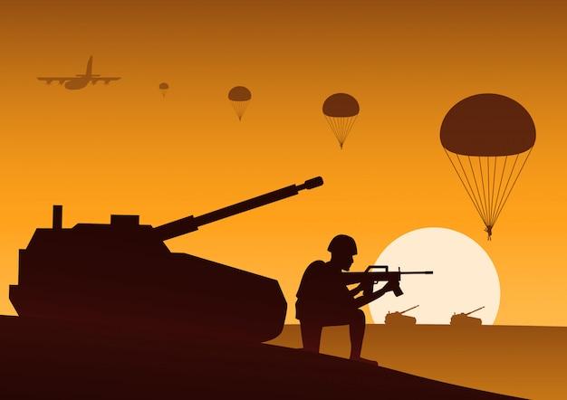 Soldado sentado cerca del tanque listo para disparar paracaidista