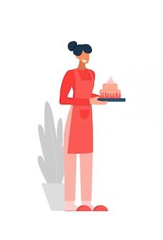 Sonriente personaje femenino doméstico en delantal con pastel de panadería casera aislado en blanco