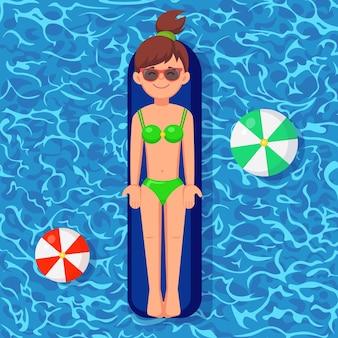 Sonrisa chica nada, bronceado en colchón de aire en la piscina.