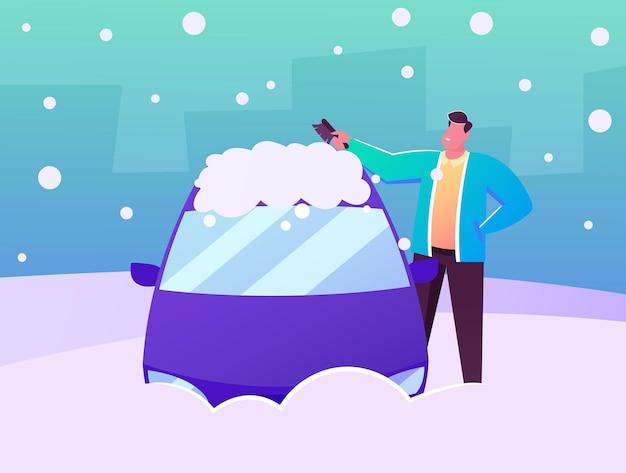Soporte de carácter de conductor de hombre en la limpieza automática de la ventana y el techo del coche con cepillo de hielo y nieve en invierno después de la ventisca nocturna