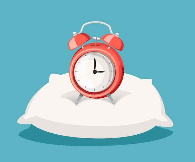 Soporte de despertador rojo sobre almohada blanca