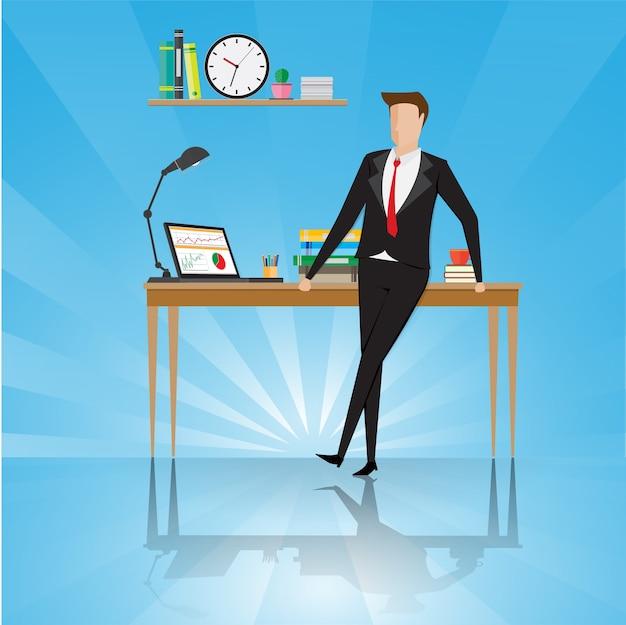 Soporte del hombre de negocios cerca de la tabla en un lugar de trabajo de la oficina.