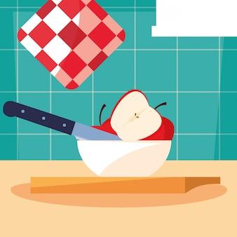Tabla de cocina con manzanas en un tazón y cuchillo