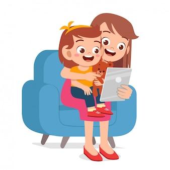 Tableta de juego de niña linda feliz niño con mamá