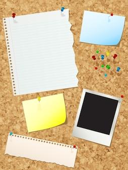 Tablón de anuncios de corcho con varios pedazos de papel y alfileres de empuje