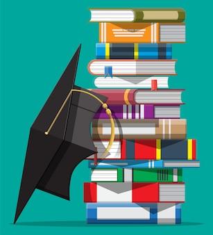 Tapa de graduación en pila de libros