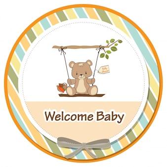 Tarjeta de baby shower con oso de peluche en un columpio