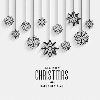 Tarjeta blanca de feliz navidad con diseño de copos de nieve colgantes