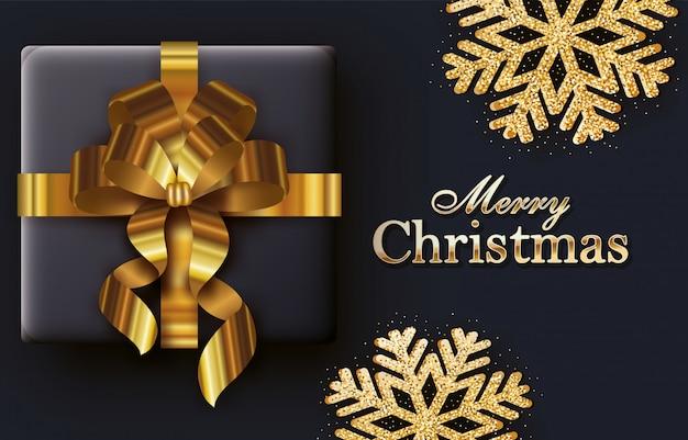 Tarjeta de caligrafía feliz navidad con regalo y cinta dorada