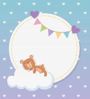 Tarjeta circular de baby shower con oso de peluche en nube y guirnaldas.