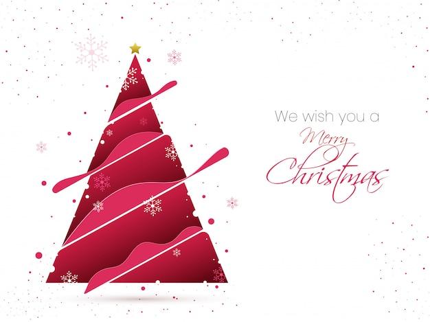 Tarjeta de deseos de feliz navidad con papel rosa cortado árbol de navidad, estrella y copos de nieve decorados en blanco.