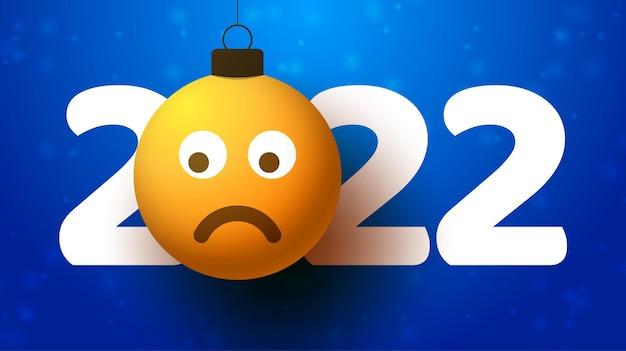 Tarjeta de felicitación para el año nuevo 2022 con cara de emoji triste que cuelga de hilo como un juguete, bola o adorno navideño. ilustración de vector de concepto de emoción de año nuevo
