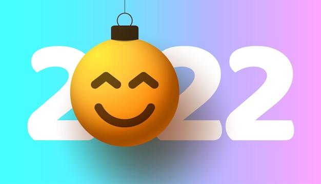 Tarjeta de felicitación para el año nuevo 2022 con cara sonriente de emoji que cuelga de hilo como un juguete, bola o adorno navideño. ilustración de vector de concepto de emoción de año nuevo