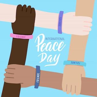 Tarjeta de felicitación del día internacional de la paz. cuatro manos de personas de diferentes razas y cruzadas juntas. amistad mundial.