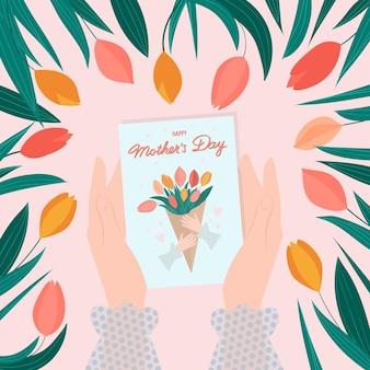 Tarjeta de felicitación del día de las madres felices en manos femeninas con tulipanes