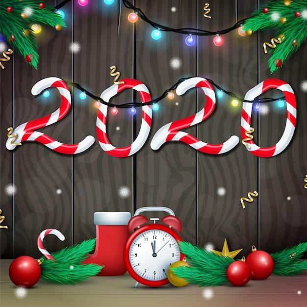 Tarjeta de feliz año nuevo 2020 sobre fondo de madera con guirnaldas de luces brillantes y ramas de pino o abeto
