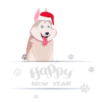 Tarjeta de feliz año nuevo con un lindo perro husky en el sombrero de papá noel sobre las huellas en el fondo blanco