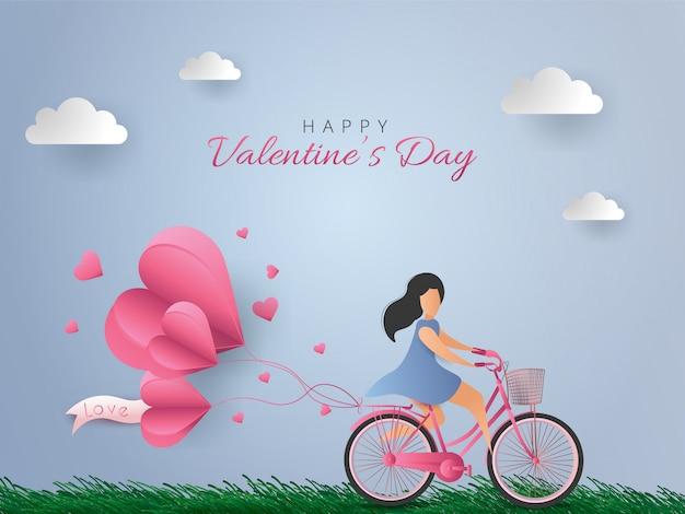 Tarjeta de feliz día de san valentín. mujer montando bicicleta con globos de aire de corazón sobre fondo de cielo azul