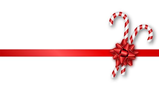 Tarjeta de regalo navideña con lazo rojo y bastones de caramelo