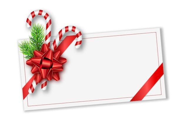 Tarjeta de regalo navideña con lazo rojo, ramas de abeto y bastones de caramelo