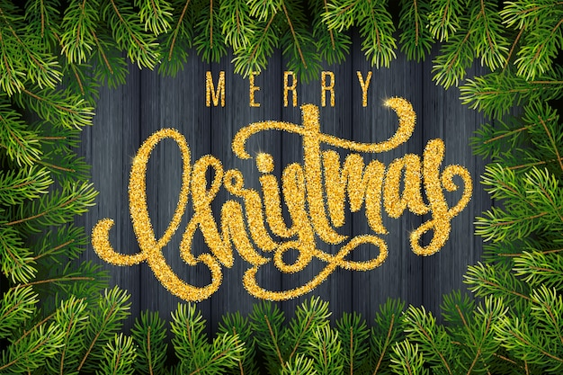 Tarjeta de regalo navideña con letras doradas a mano feliz navidad y ramas de abeto sobre fondo de madera oscura.