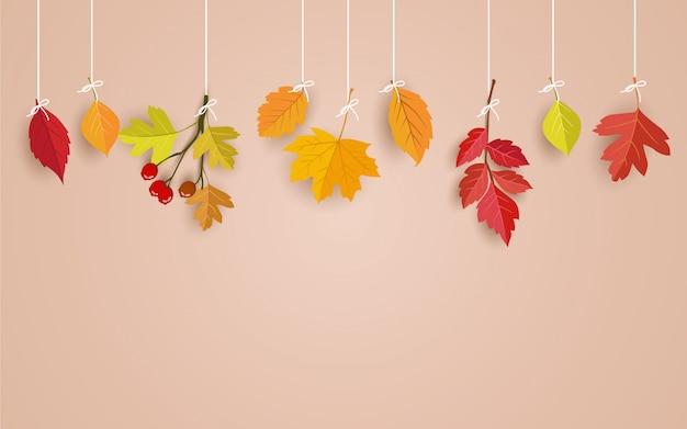Tarjeta rosa con hojas de otoño colgando de un hilo