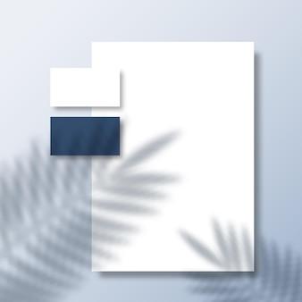 Tarjetas de visita y papel con membrete en una superficie con una superposición de sombra de hojas de palmera de helecho tropical