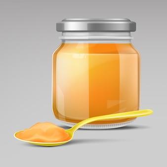 Tarro de comida para bebé de vidrio y cuchara de plástico con puré