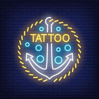 Tatuaje de neón de la palabra y el signo de anclaje. anuncio brillante de la noche, letrero colorido