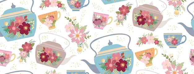 Taza de té y tetera hermosas con la flor y las hojas aisladas en blanco
