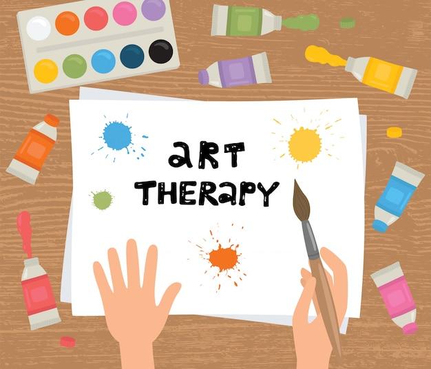 Terapia artística. manos, pincel, pintura, hoja de papel sobre un fondo de madera.