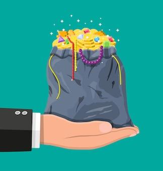 Tesoros en bolsa en mano