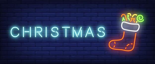 Texto de neón de navidad y bota de fieltro con regalos
