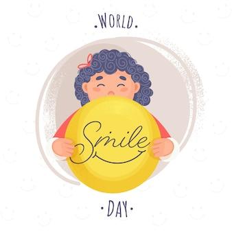 Texto del día mundial de la sonrisa con niña de dibujos animados sosteniendo una cara sonriente y efecto de pincel de ruido marrón sobre fondo blanco