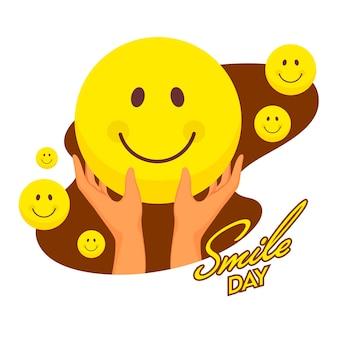 Texto del día de la sonrisa del estilo de la etiqueta engomada con la mano que sostiene el emoji sonriente en fondo marrón y blanco.