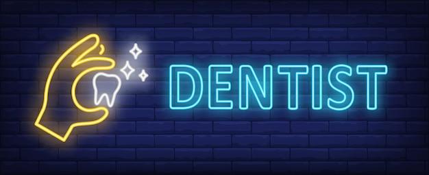 Texto de neón del dentista con la mano que sostiene el diente que brilla intensamente