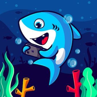 Tiburón lindo jugando ilustración de dibujos animados de teléfono inteligente